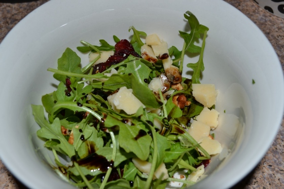 Arugula salad with balsamic reduction and parmesan, dried cranberries and candied nuts